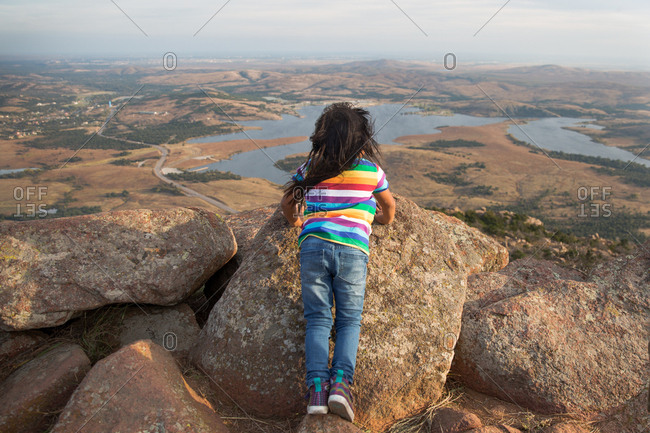 Girl looking out at scenic view from mountaintop