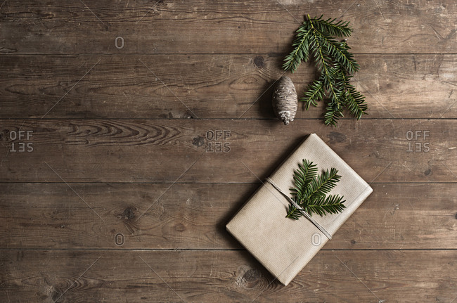 Christmas present decorated with pine needle twigs and pine cone on wooden table
