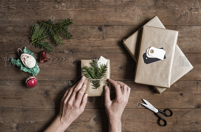 Person decorating Christmas present with pine needle twigs