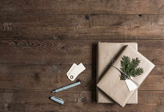Christmas presents, gift tags, and pen on wooden table