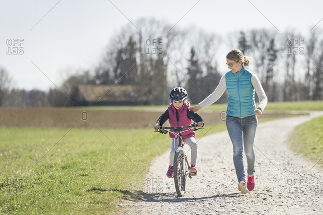 Mother assisting daughter riding bicycle on footpath amidst field