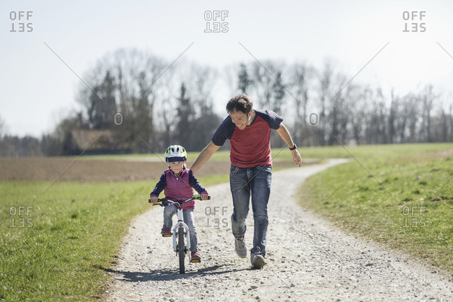Father assisting daughter riding bicycle on footpath amidst field
