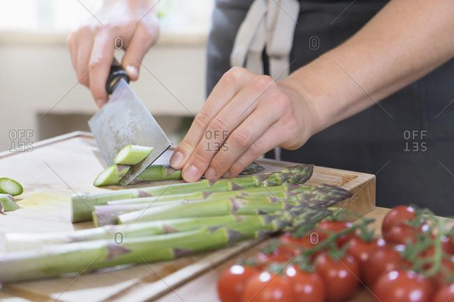 Man cutting asparagus on wooden board