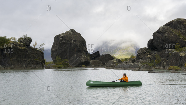 Laitaure delta, Sweden - September 3, 2016: Woman canoeing on a small lake in the early autumn