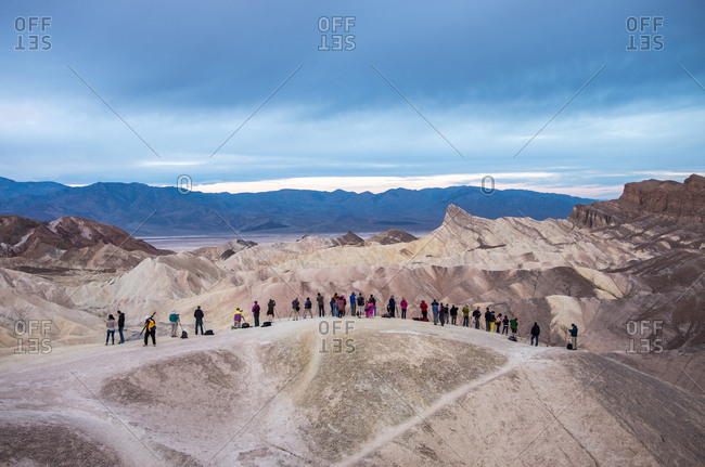 Death Valley, Death Valley National Park, California, United States of America - March 5, 2016: Tourists standing at an overlook at Zabriskie Point in Death Valley National Park