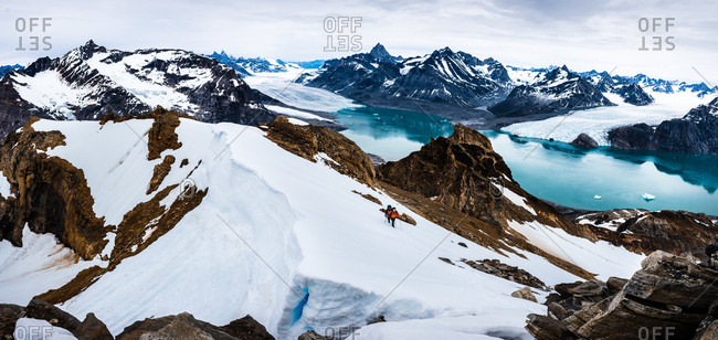 Eastern Greenland, Sermersooq, Greenland - July 20, 2017: Panorama view of two climbers making their way over a snow-covered ridge