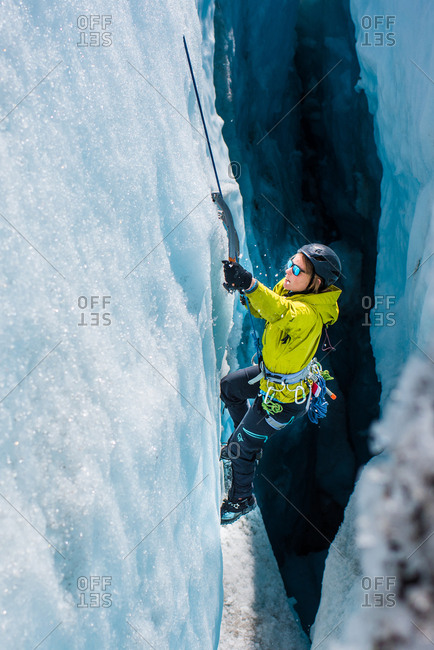 A woman in yellow jacket and sunglasses ice climbing up through a crevasse inside a glacier