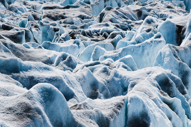 The surface of a glacier, with black, blue and white snow