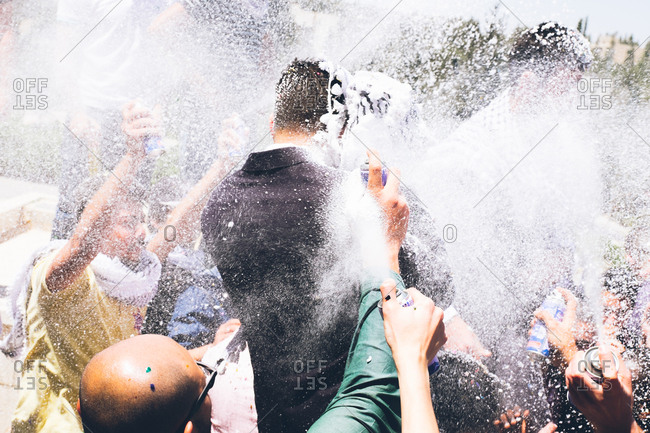 People spraying man with foam in celebration