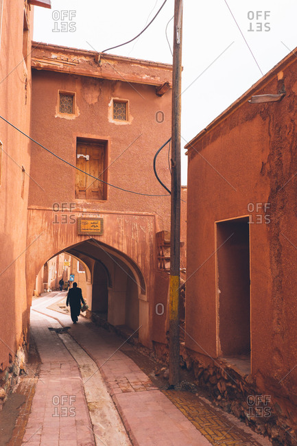 Abyaneh, Iran - December 29, 2016: Man walking under archway of red buildings in streets of Abyaneh, Iran