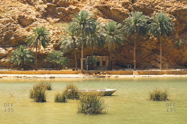Small boat moored in a river in the canyons of Wadi Shab, Oman