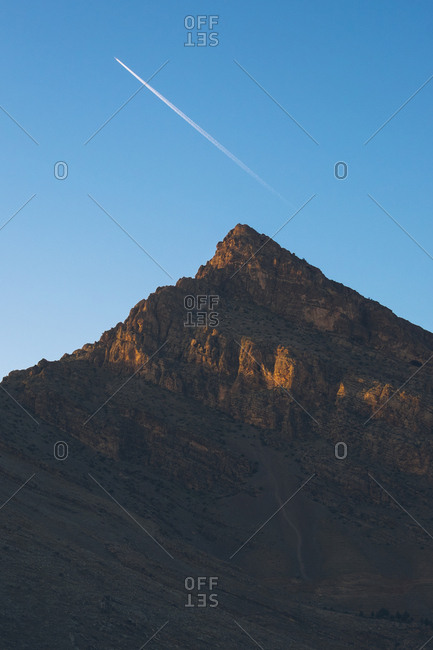 Jet plane flying in blue sky over the Zagros mountains