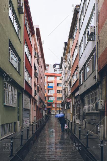 Istanbul, Turkey - February 5, 2017: Pedestrian walking down a narrow rainy street in Istanbul