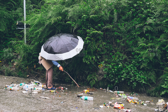 Manali, Himachal Pradesh, India - June 21, 2017: Man with stick standing in pile of trash on road