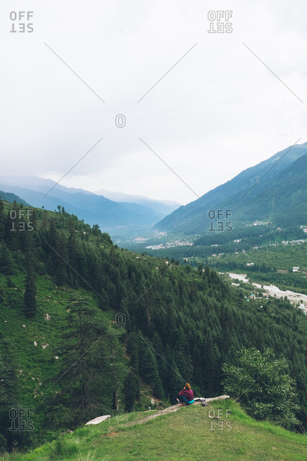 Woman overlooking forest in Himachal Pradesh, India