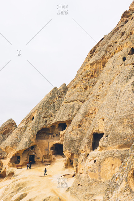 Cappadocia, Turkey - February 12, 2017: Tourists visiting houses carved in stone in Cappadocia, Turkey