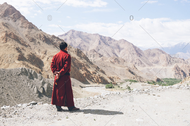Man in red coat overlooking mountains in Leh, Ladakh, India