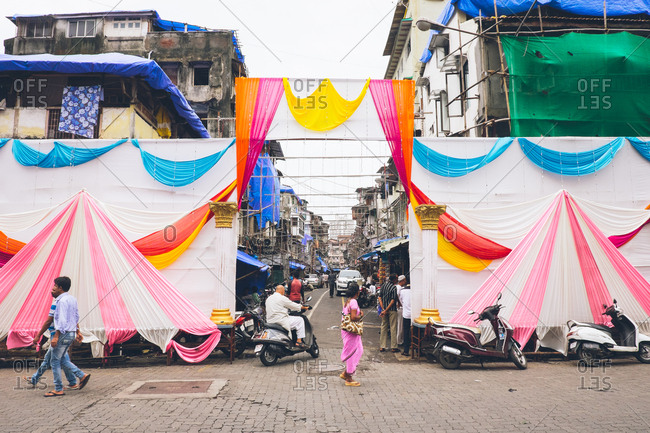 Mumbai, India - July 2, 2017: Brightly colored tents and fabric decorate the entrance to a busy street market
