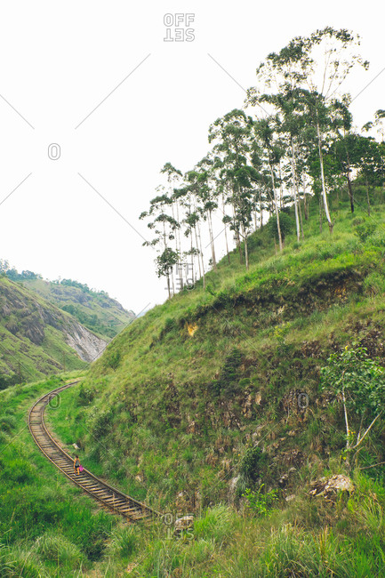 Woman hiking on train tracks through hills of Ella, Sri Lanka