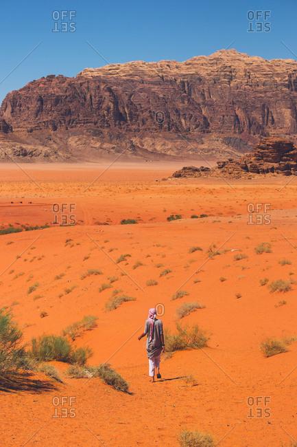 Rear view of man walking in the Wadi Rum desert, Jordan