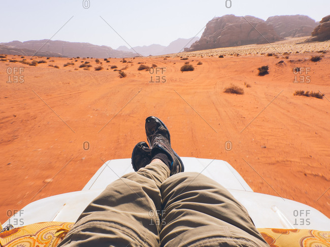 Wadi Rum desert, Jordan - April 5, 2017: View of man's legs sitting on vehicle in the Wadi Rum desert