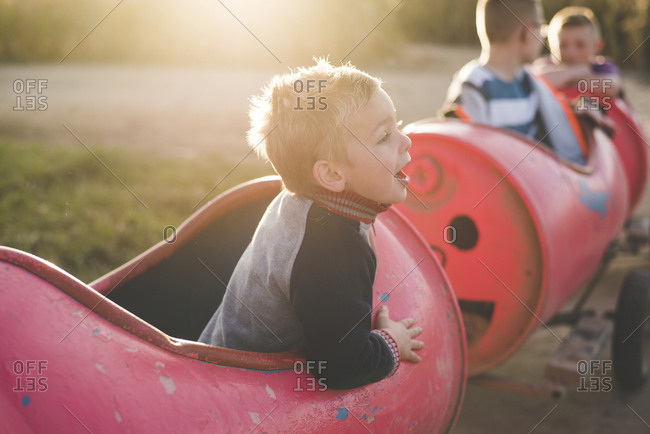 Side view of boy shouting while sitting in toy train