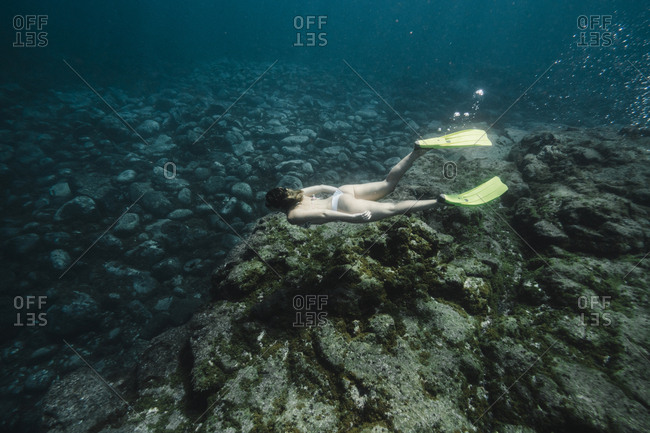 High angle view of carefree woman scuba diving undersea