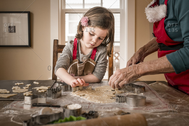 Granddaughter helping grandmother in making Christmas cookies on table at home