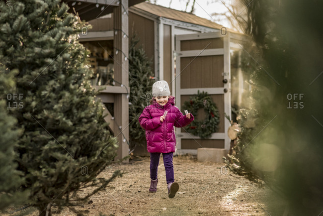 Cheerful girl holding candy canes walking by Christmas Trees at yard