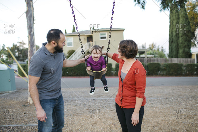 Father and mother swinging daughter on swing at playground