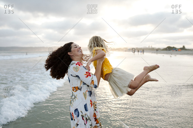 Playful mother spinning daughter at beach