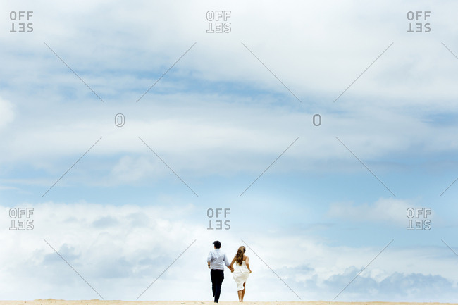 Rear view of newlywed couple running at beach against cloudy sky
