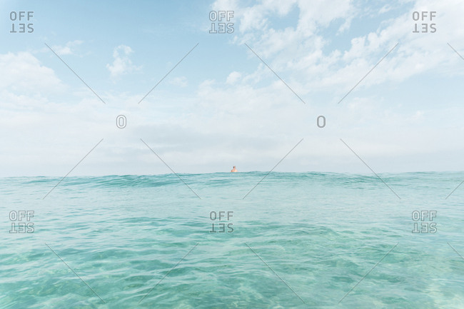 Mid distance view of man swimming in sea against sky
