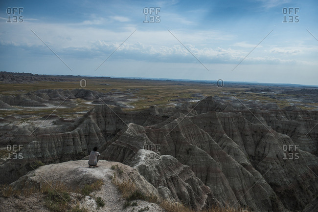 High angle view of hiker crouching on rocks at Badlands National Park against sky