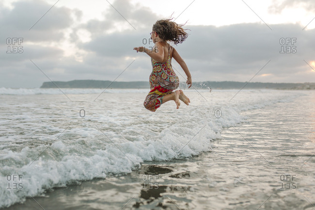Side view of playful girl jumping at beach against cloudy sky