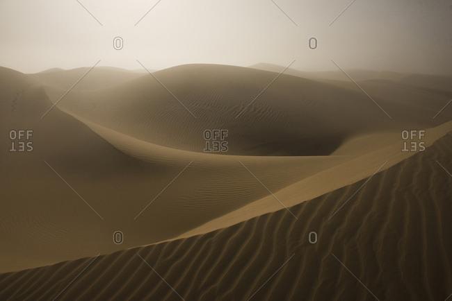 Idyllic view of sand dunes against sky at desert