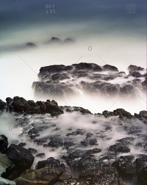 High angle view of rocks in sea during foggy weather