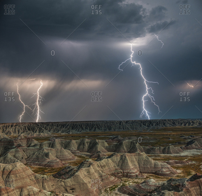 High angle majestic view of rock formations at Badlands National Park against thunderstorm and lightning