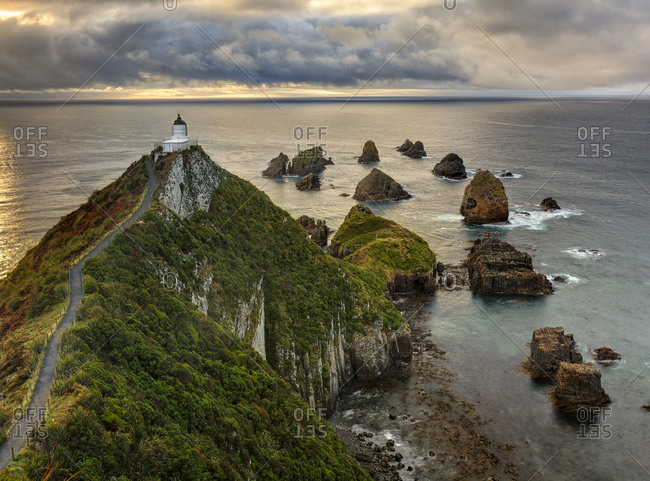 Nugget Point (Ka Tokata) lighthouse at sunrise, rain clouds sweeping in from the horizon. Catlins, Clutha District, Otago, South Island, New Zealand. October, 2006.