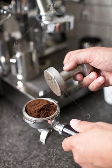 Barista tamping espresso coffee