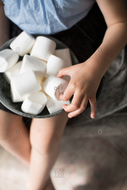 Close-up of girl holding a bowl full of marshmallows candy