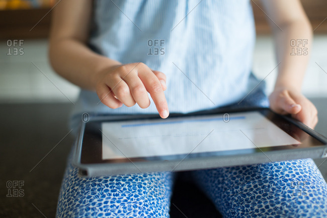 Close-up of girl operating digital tablet at home