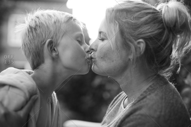 Mother and son kissing outdoors