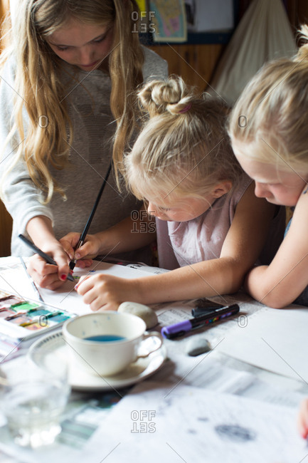Girls drawing and water coloring together on paper