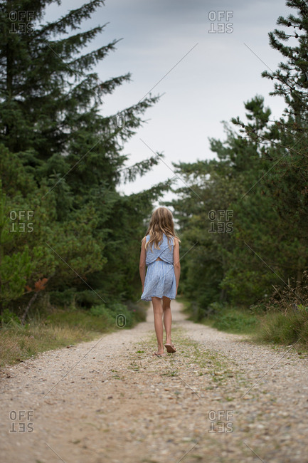 Rear view of girl walking alone in desolate forest