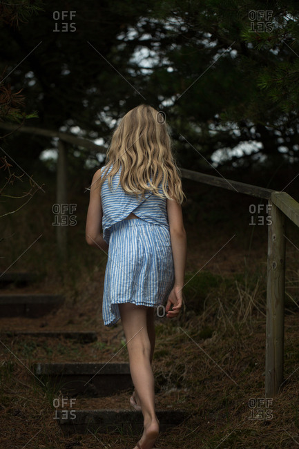 Rear view of girl climbing steps in forest