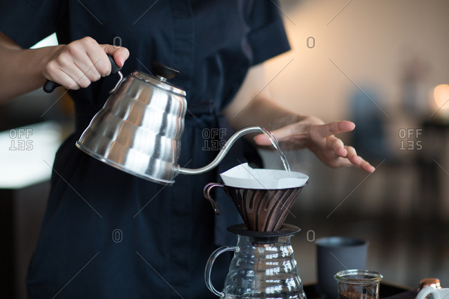 Woman pouring hot water from kettle into coffee filter