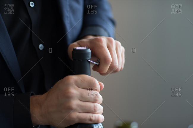 Man opening wine bottle using corkscrew knife