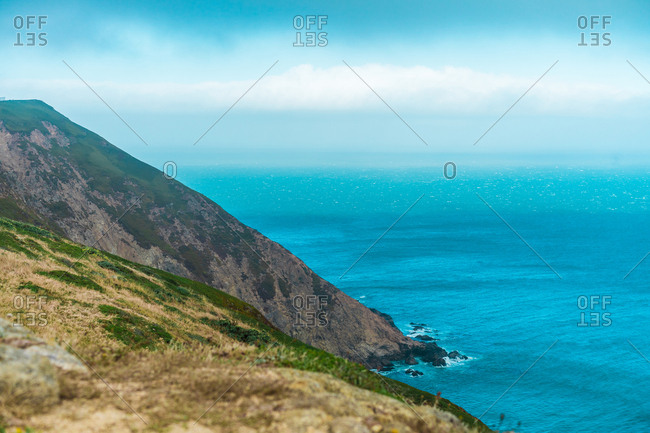 Landscape of mountains on coastline of ocean with turquoise water.