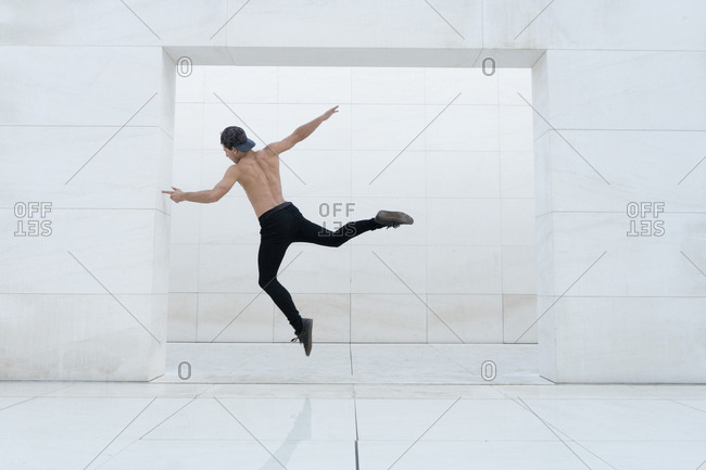 Back view of shirtless man jumping in doorway of white tiled room.